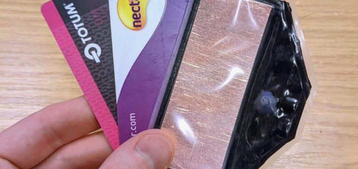 La bomba electro-neumática (derecha) junto con tarjetas de billetera para escala
